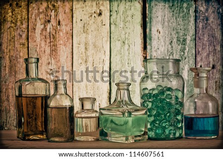 Old laboratory glass in front of grunge wooden background