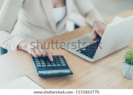 Old lady boss accountant typing on netbook, calculating finance, profit, plan on calculator, work place work station