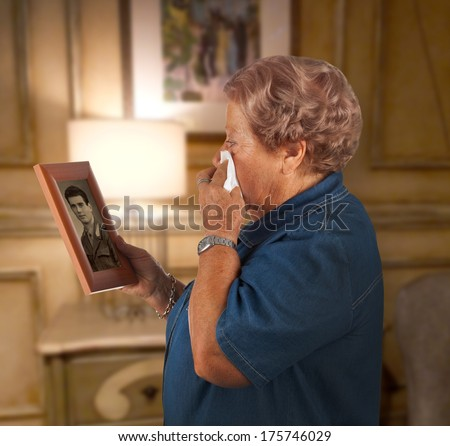 Old lady crying watching a photo of a deceased person.