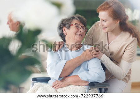 Old lady in glasses sitting in a wheelchair and smiling at her nurse