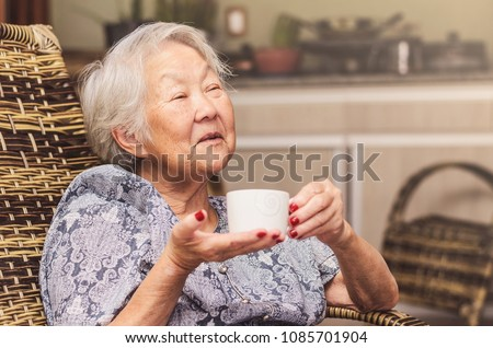 Old lady (japanese descendant) seated comfortably at home holding a cup of tea with a happy expression of who is having a good conversation or telling stories. #1085701904