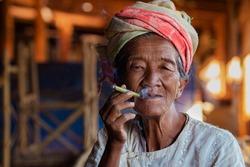 Old lady of Pa'O ethnic minority smoking a Burmese cigar at Indein village near Inle Lake, Shan State, Myanmar.