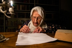 Old lady reading books in dark room with candles light and writing down some notes