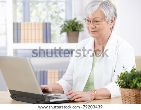 Old lady sitting at desk at home, using laptop.?