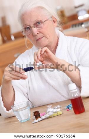 Old lady taking medication - stock photo