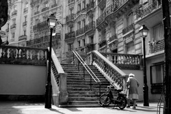 Old lady walking in a street of Montmartre in Paris walking up old stairs in art deco style. Black and white image expressing loneliness.