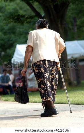 Old lady walking up a  hill with  cane