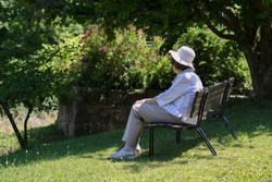 old lady with hat sitting and resting on a parkbench