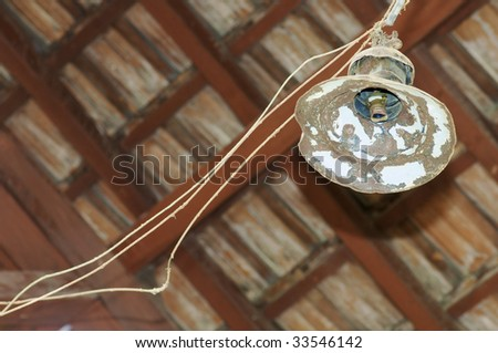 old lamp hanging from a wooden ceiling