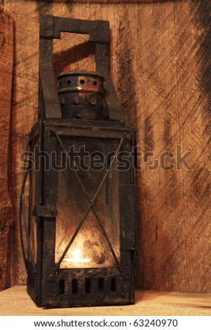 Old lamp with lighted candle on wooden background