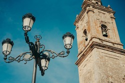 Old lamppost with church steeple in Spain, Europe.
