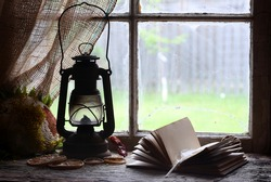 Old lantern and book on shelf by window