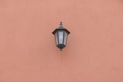 Old lantern with a white lamp. Wall color - Oriental Pink, Hue Red. Vintage lantern concept.