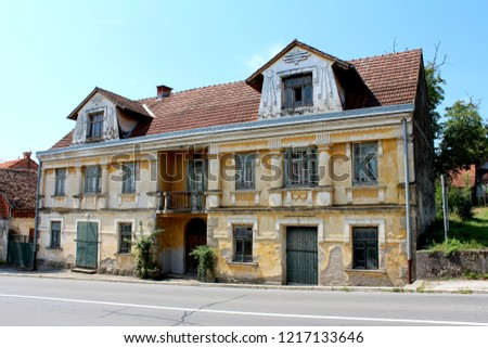 Old large abandoned baroque style family house with cracked dilapidated facade, broken windows and locked doors next to asphalt road with clear blue sky in background