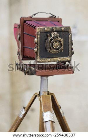 Old large format photo camera on a tripod on the street outdoors. Stock photography.