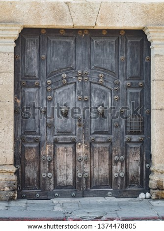 Old, large wooden double door, with Gothic knockers and other architectural details, in Antigua, Guatemala
