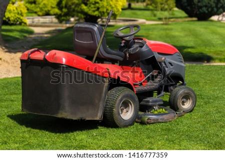 Old Lawn mower cutting green grass in backyard.Gardening background.  #1416777359