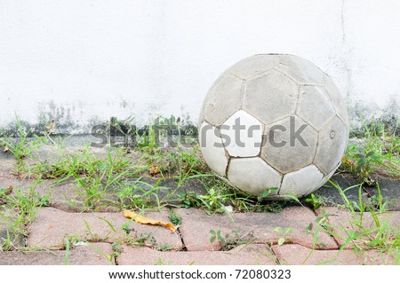 Old leather ball on the brick near the football ground.