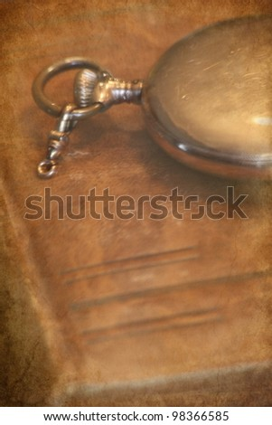 old leather book cover and pocket watch