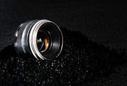 old lens on black sand