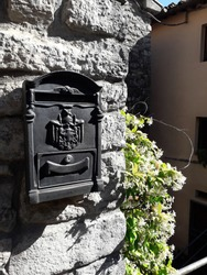 Old letter box on wall  of one house of stones with climbed flowers in the street of village