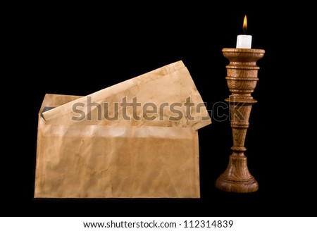 old letters and candle on a black background