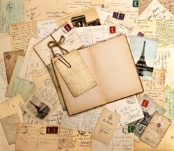 old letters, french post cards and empty open book. nostalgic vintage background