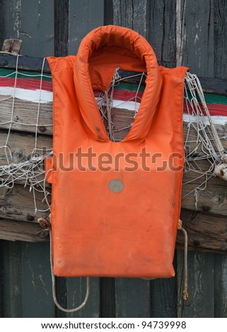 old life jacket on the background of a fishing net and boat wreckage - stock photo
