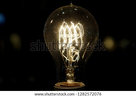 old light bulb glowing in dark . Close up #1282572076