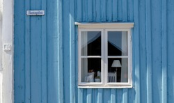 old lightblue wooden exterior wall of a house with white window in the hamngatan (harbor street) of Västervik, Sweden
