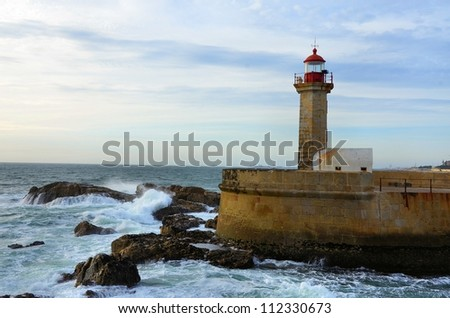 Old lighthouse and the sea hitting the rocks