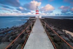 Old lighthouse in Gardur, Keflavik, Iceland. Cloudy Sky and choppy sea. Beautiful sunset