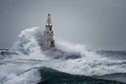 Old Lighthouse In Stormy Landscape. Storm waves over the Lighthouse -Ahtopol, Black Sea, Bulgaria.