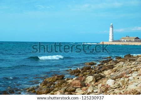 Old lighthouse on the sea coast. Storm, waves and blue sky.