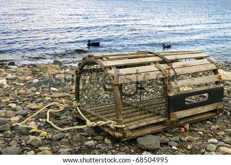 Old Lobster Trap: old handmade wooden lobster trap on pebble beach in the Maritime Provinces of Canada
