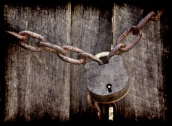 old lock and chain around wooden fence