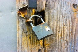 Old lock hanging on a wooden wall or brown door close-up. A rusty vintage style barn copper lock. A metal antique device for closing doors. Protection against burglars and thieves. High quality photo.