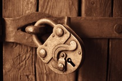 Old lock hanging on wooden door. vintage, aged Padlock. rusty lock hang on a wooden gate
