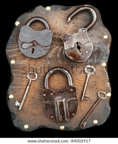 Old locks and keys on wooden plank isolated on black. Clipping path included.