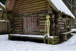 Old log house between trees in the winter. Vintage agriculture equipment hanging on the timber wall. Human shape sculpture.Mossy roof covered with snow. Tavern farm in Mustjoe, Estonia, Baltic, Europe