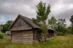 Old log hut. Ingrown grass. Overcast sky. Slate roof.