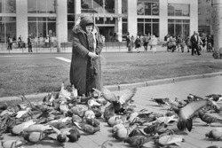 Old lonely woman feeding birds in the center of the big city. People crossing by. Concept of kindness.