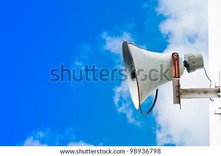 Old loudspeaker against  blue sky