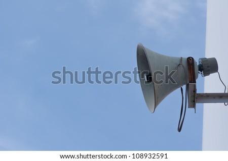 Old loudspeaker against cloudy blue sky