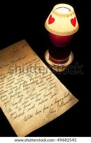Old love letter and romantic candle burning on a black background