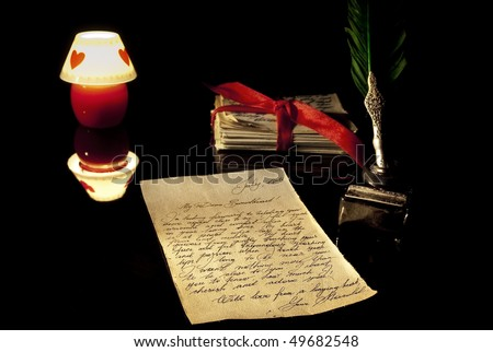Old love letter, antique quill, stack of letters tied with a red ribbon and romantic candle