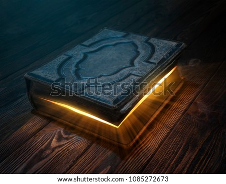 Old magic book on wooden table with light rays coming out form the inside #1085272673