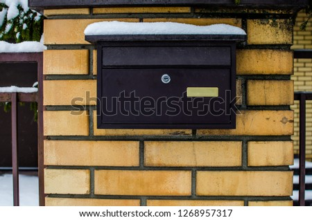 Old mailbox in winter. Metal mailbox covered with snow during a snowfall.