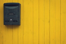 Old mailbox on a yellow wooden background, rustic style