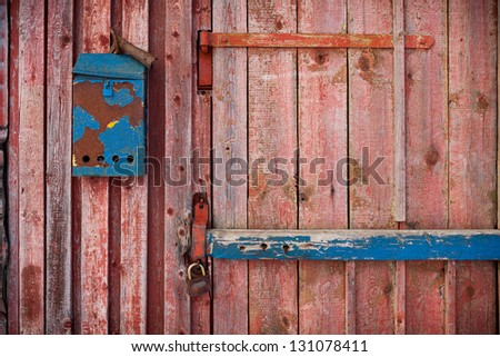 old mailboxe on an old wooden door painted red